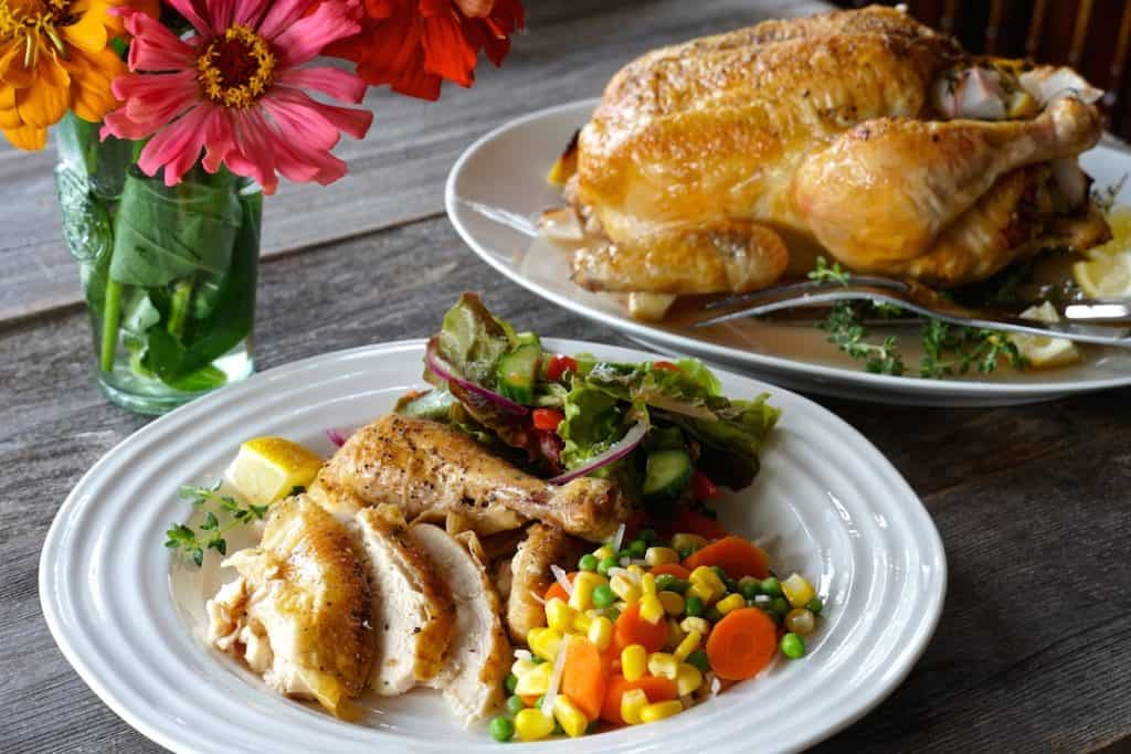 Serving roasted chicken with a salad and veggies