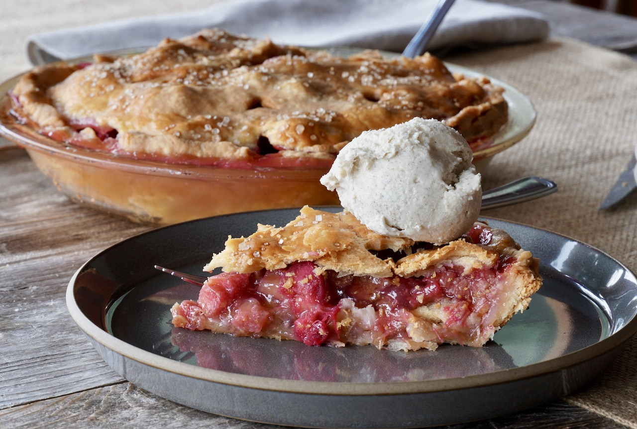 A slice of HOMEMADE RHUBARB PIE topped with vanilla ice cream