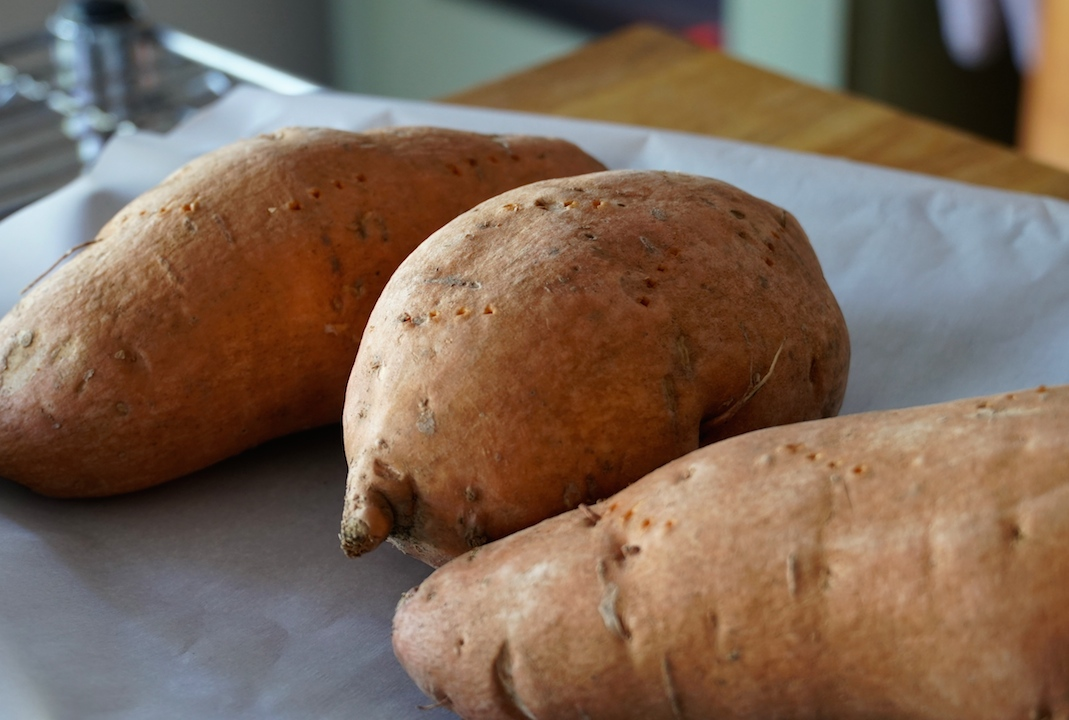 Sweet potatoes pricked with a fork, ready for the oven