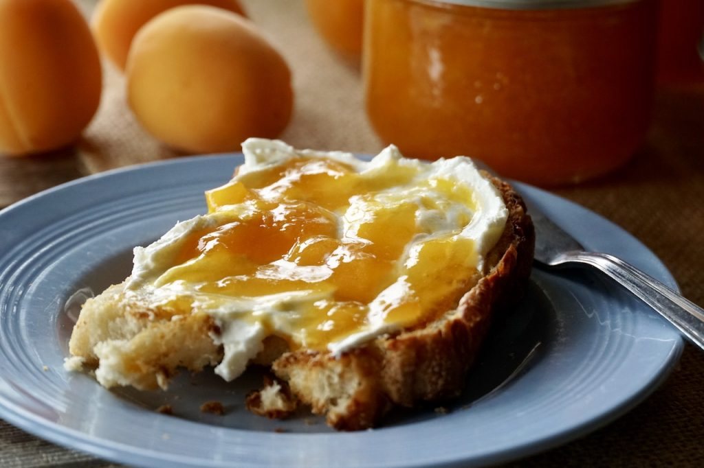 Apricot jam spread onto cream cheese covered toast