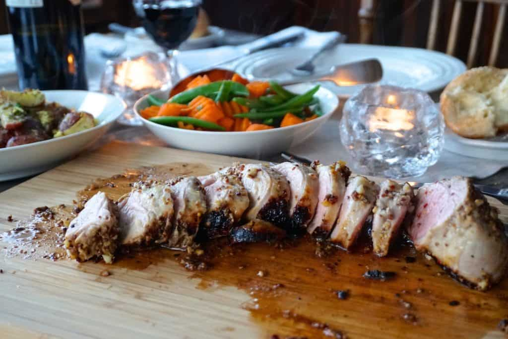 A cutting board of Oven-Roasted Pork Tenderloin served on the table