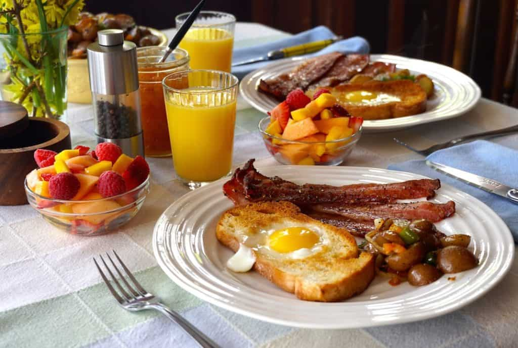 Egg in the Basket set out with freshly squeezed juice, crispy bacon, home fries and fresh fruit salad