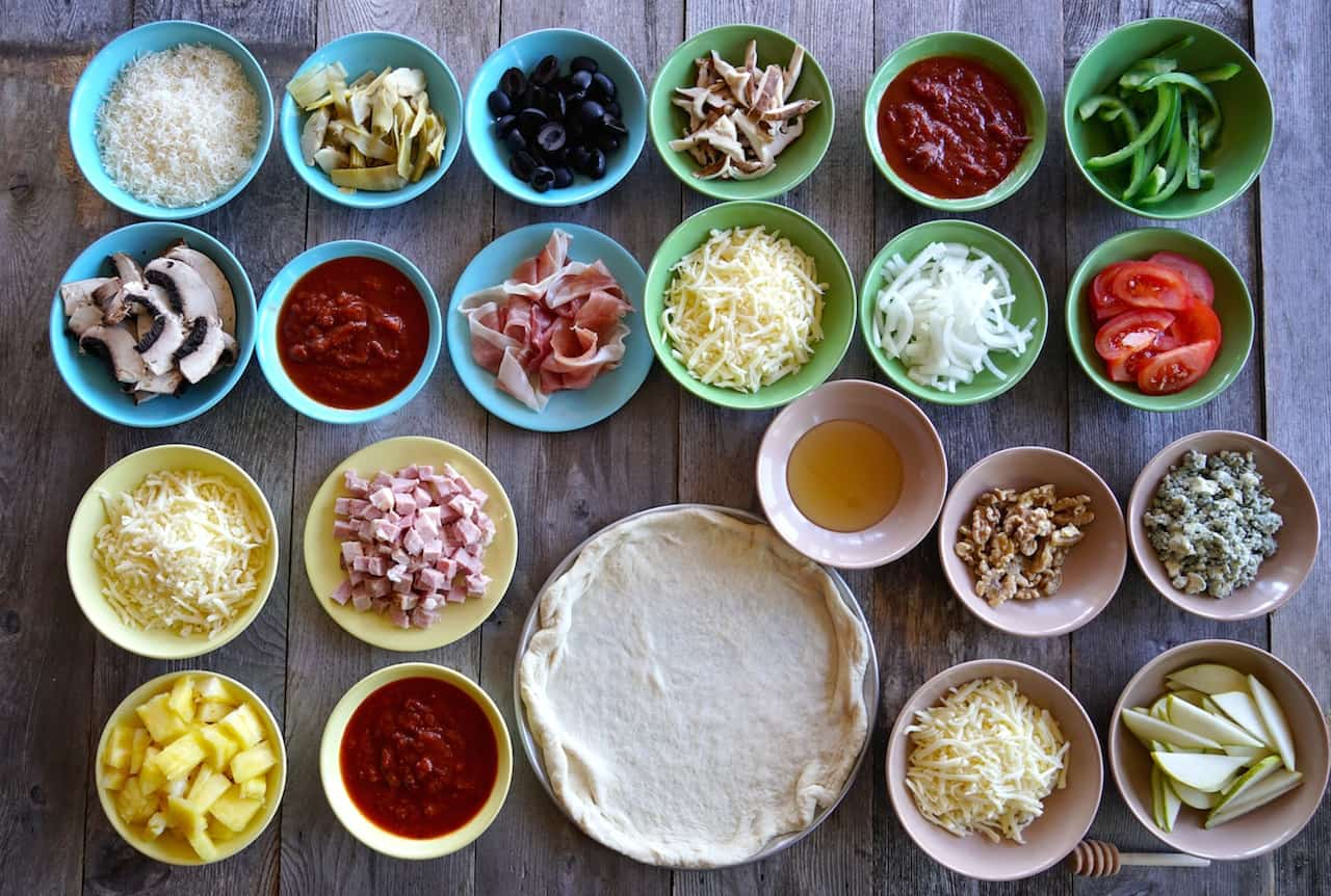 Assorted toppings set out on a make-your-own pizza station