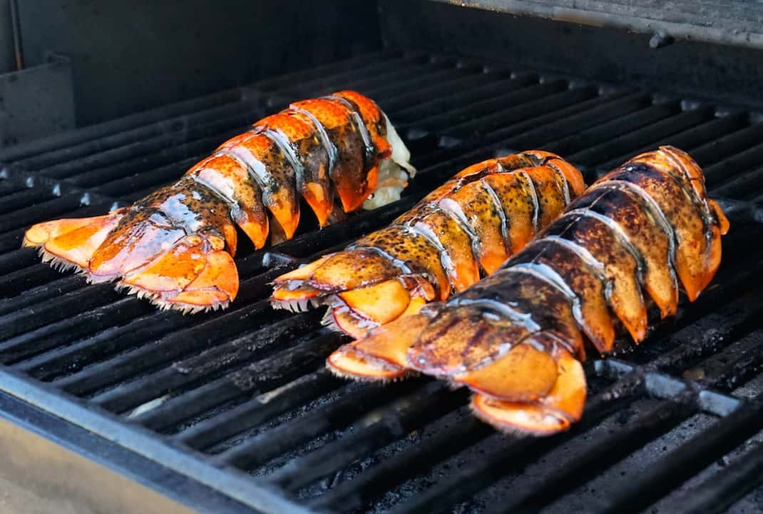 Whole lobster tails brushed with butter while on the grill