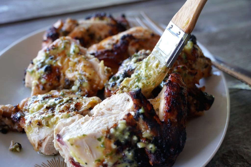 brushing the grilled chicken with extra marinade