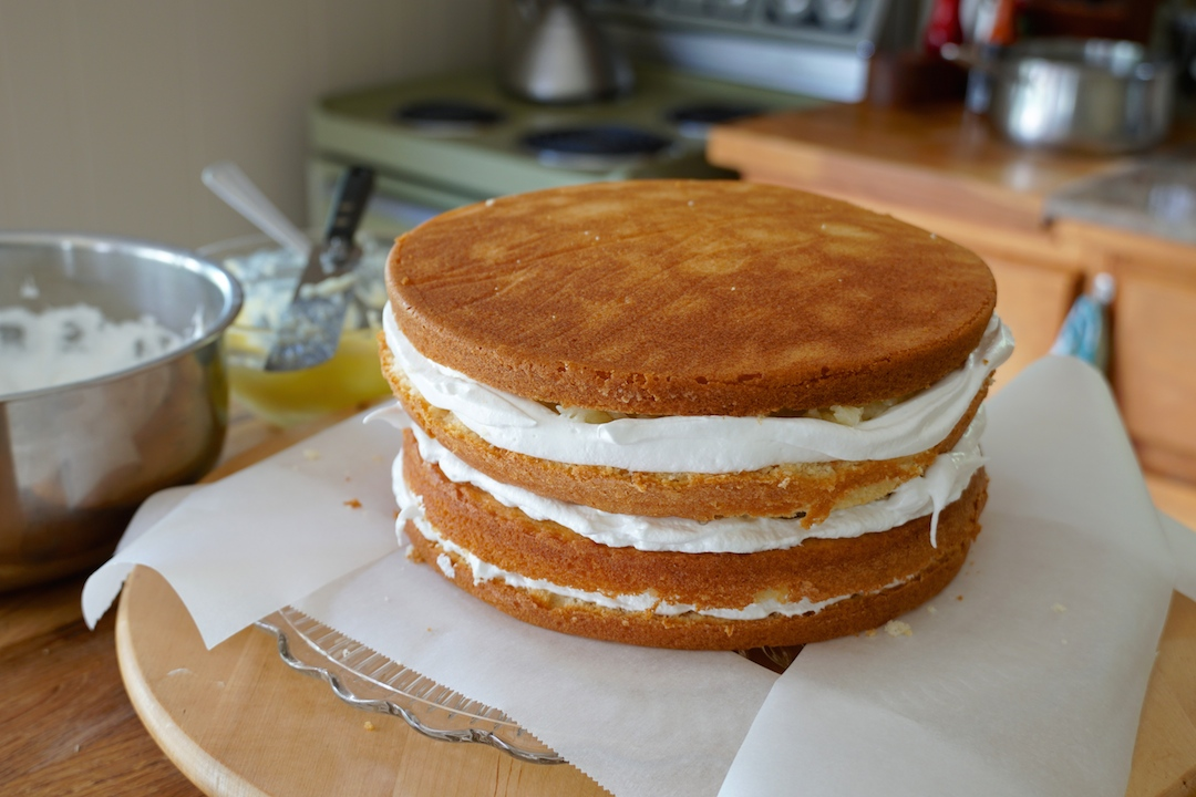 The layers of cake stacked between custard and whipped coconut frosting