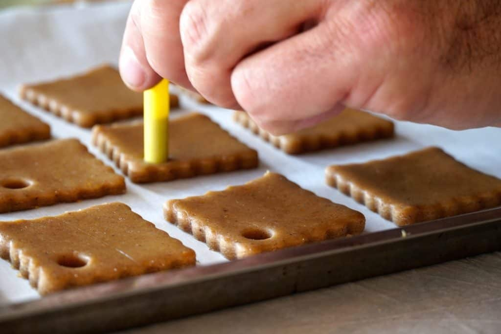 Cutting holes in the cookies to make ornaments
