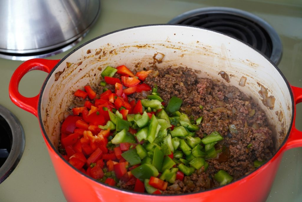 Adding the peppers into the pot