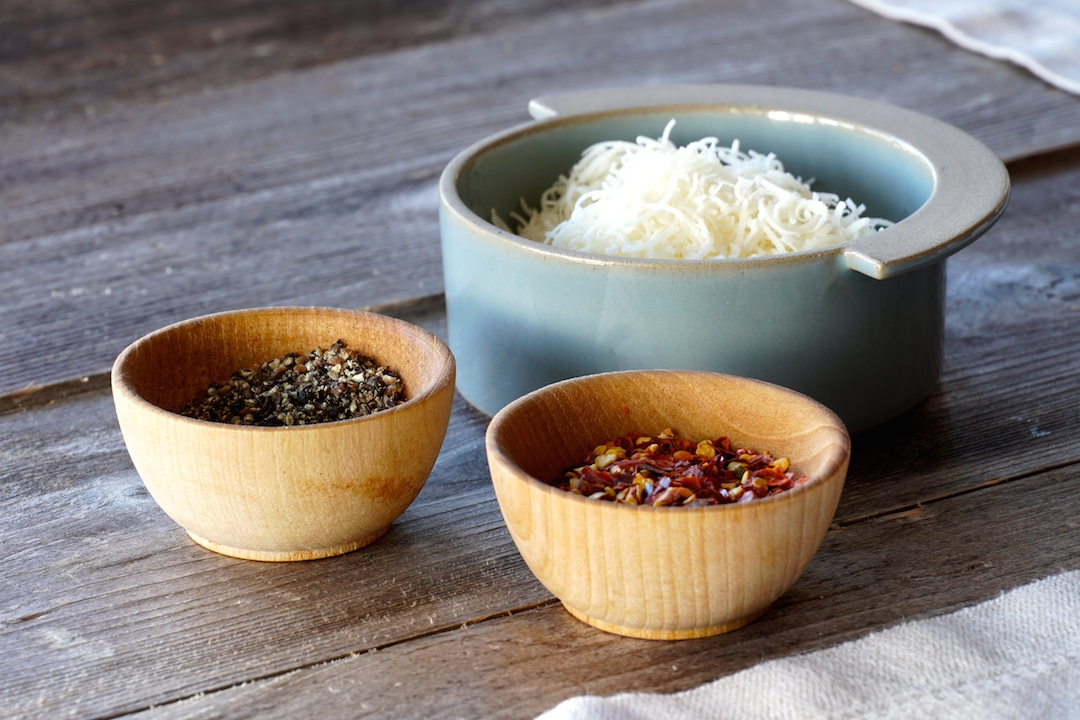 Garnish with grated Parmesan, black peper and chili flakes