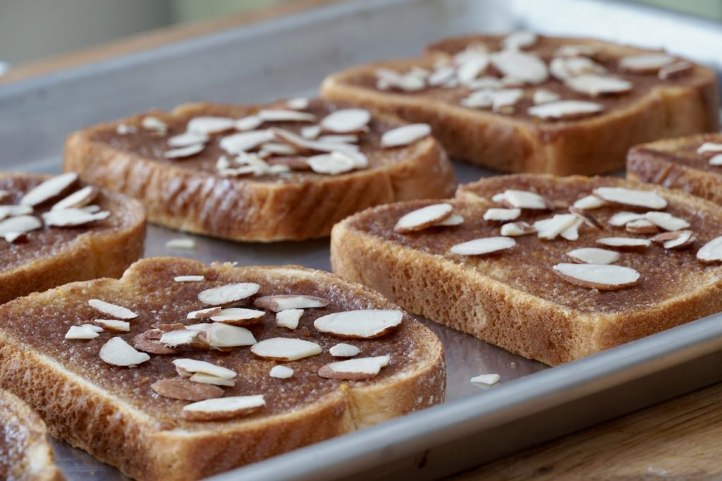 Adding sliced almonds to the baked bread
