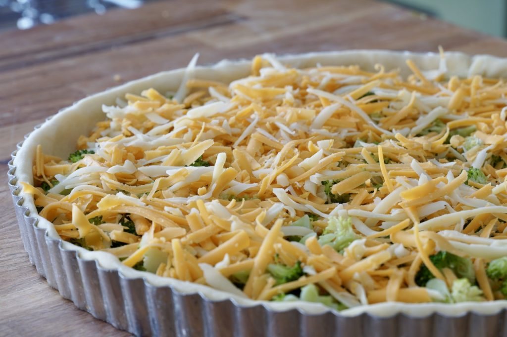 Quiche pan filled with broccoli, cheeses and onion
