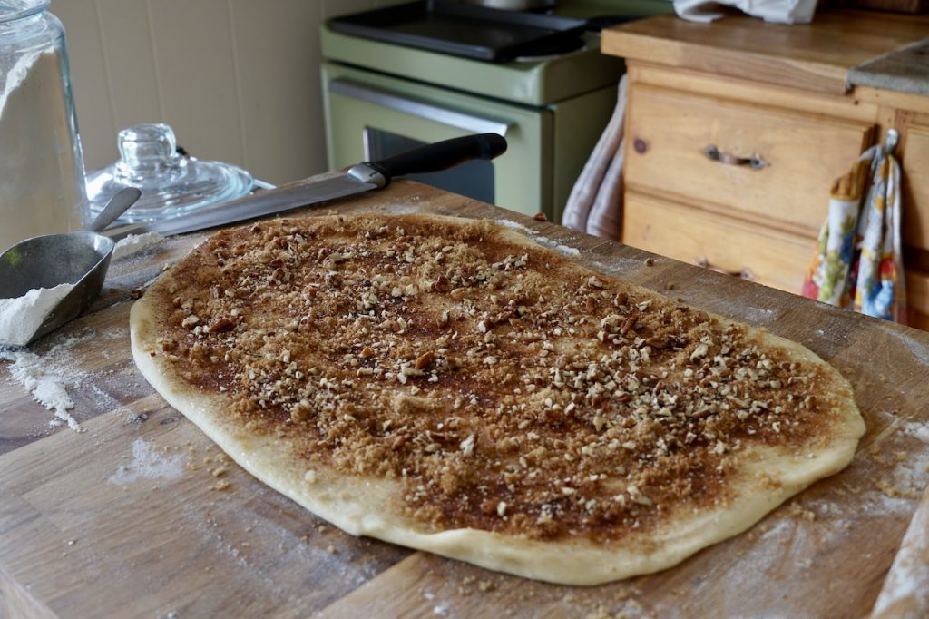 The yeast dough sprinkled with butter, cinnamon, sugar and chopped pecans