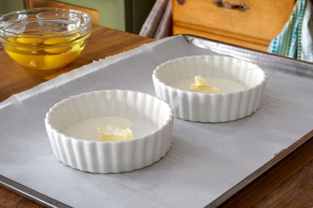 Fluted oven-safe baking dishes dotted with butter