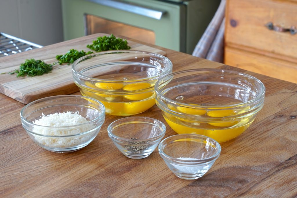 Two eggs c racked into small bowls assist with the quick transfer to the heated baking dishes.