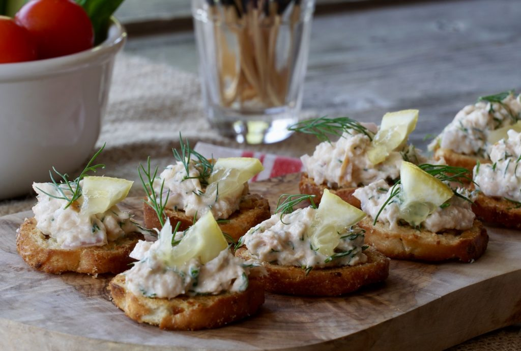 Smoked Trout Dip served as an hors d'oeuvres on small round of toast with lemon and dill garnish