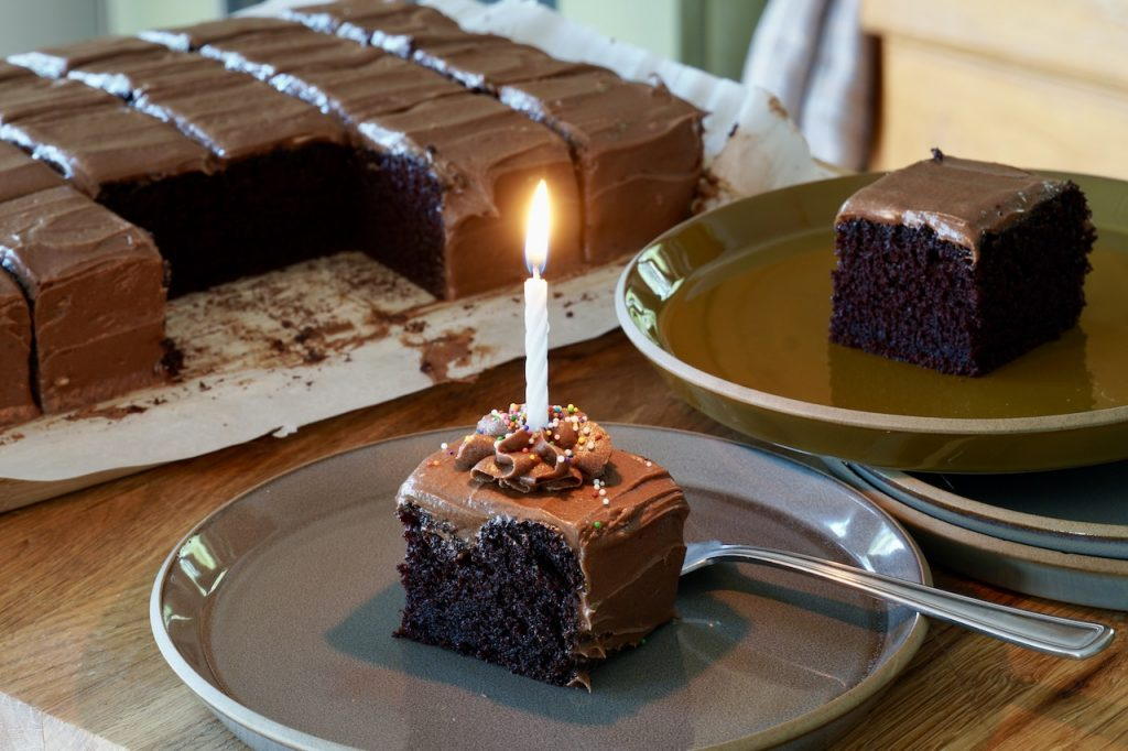 A piece of cake dressed up with sparkles and a celebratory candle