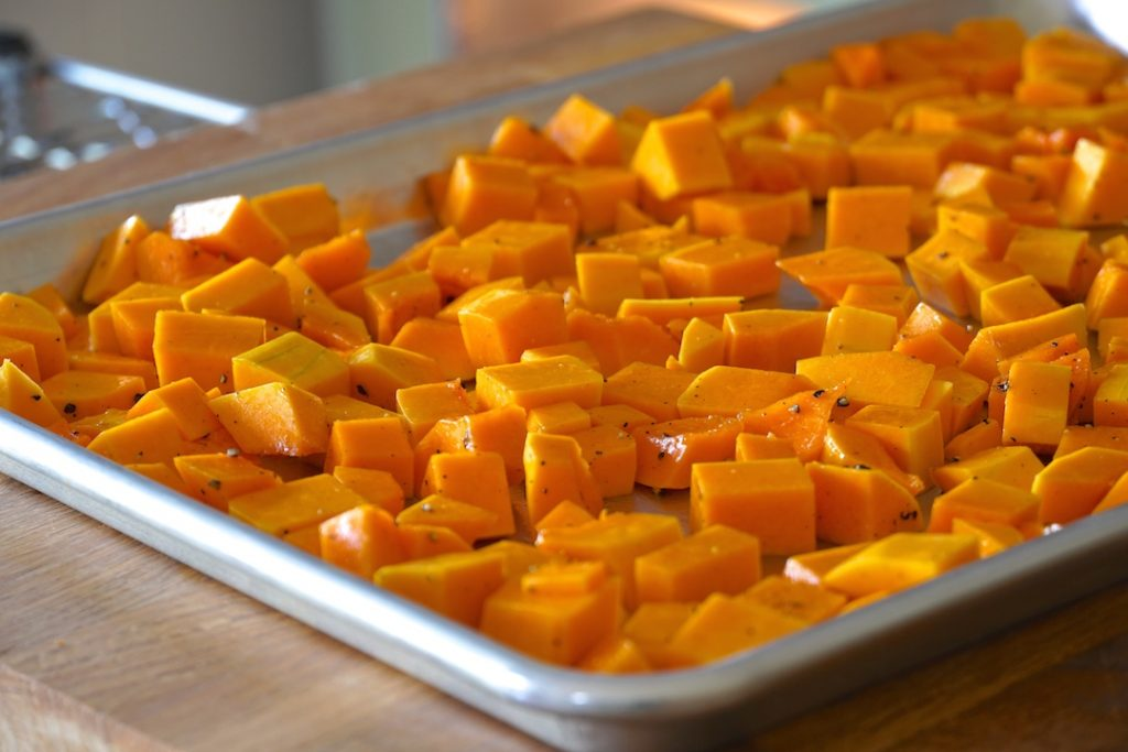 The butternut squash spread out on a baking sheet