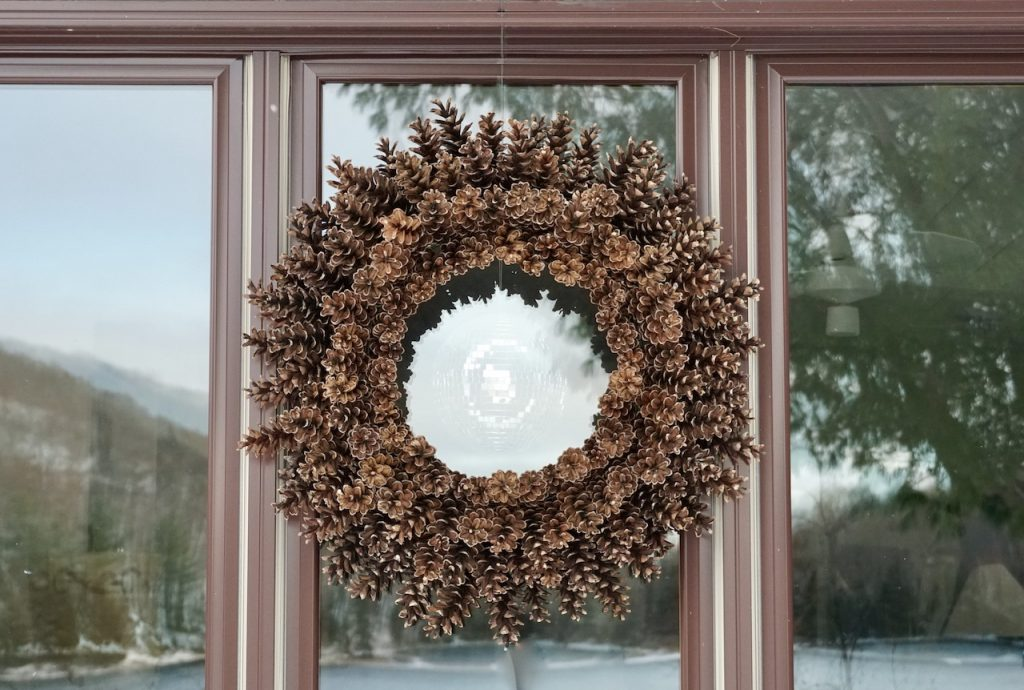 The wreath hung outdoors against a window