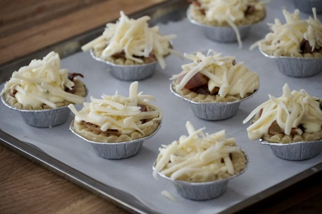 Topping the tarts with grated Gruyère