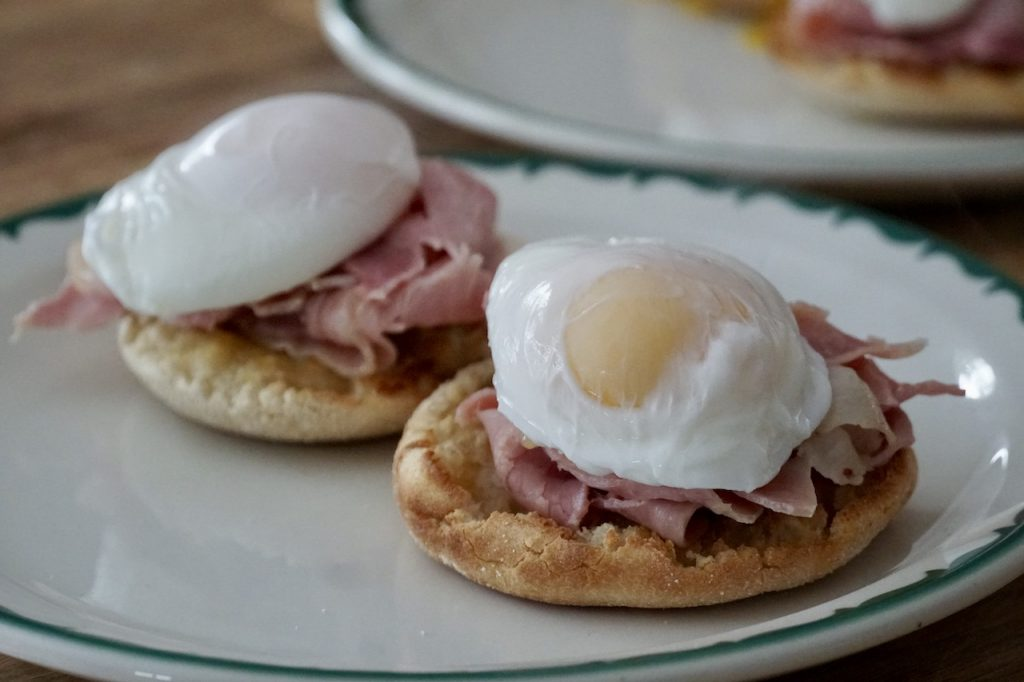 The eggs nestled in the ham resting on the toasted English muffins