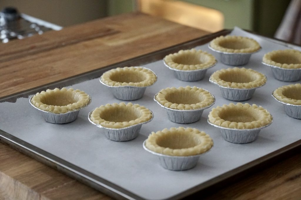 Mini tart shells lined up ready to be filled