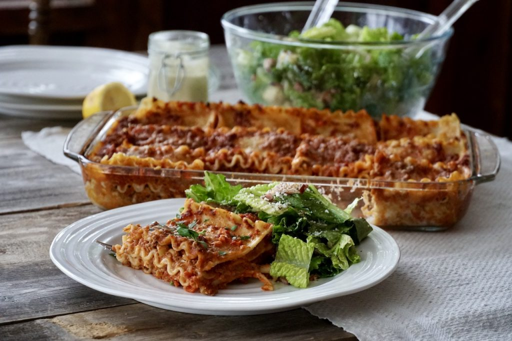 Lasagna served with a big bowl of homemade caesar salad