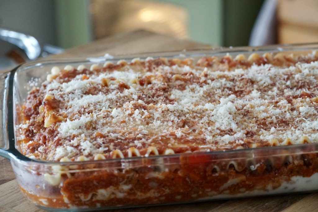 The casserole dish layered with the meat and cream sauces, cheese and noddles