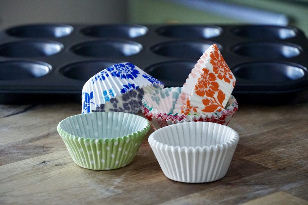 Make muffins by greasing the pans or using attractive paper liners