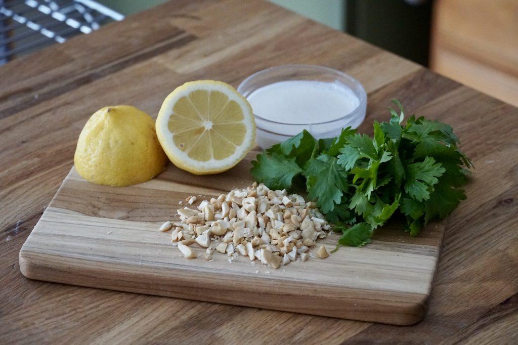 A garnish of yogurt, cashews, cilantro and lemon