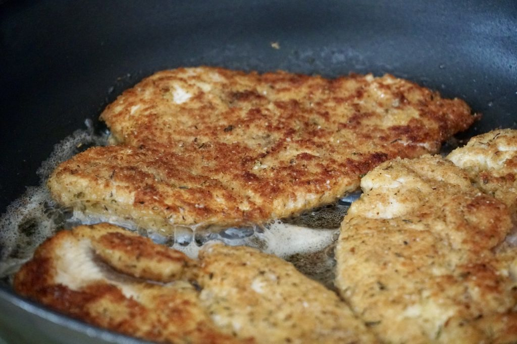 The breaded chicken sizzling in the skillet