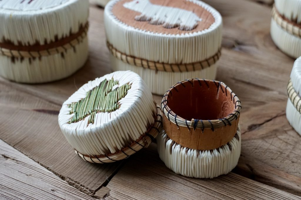 A tiny box handmade using quills, bark and twine