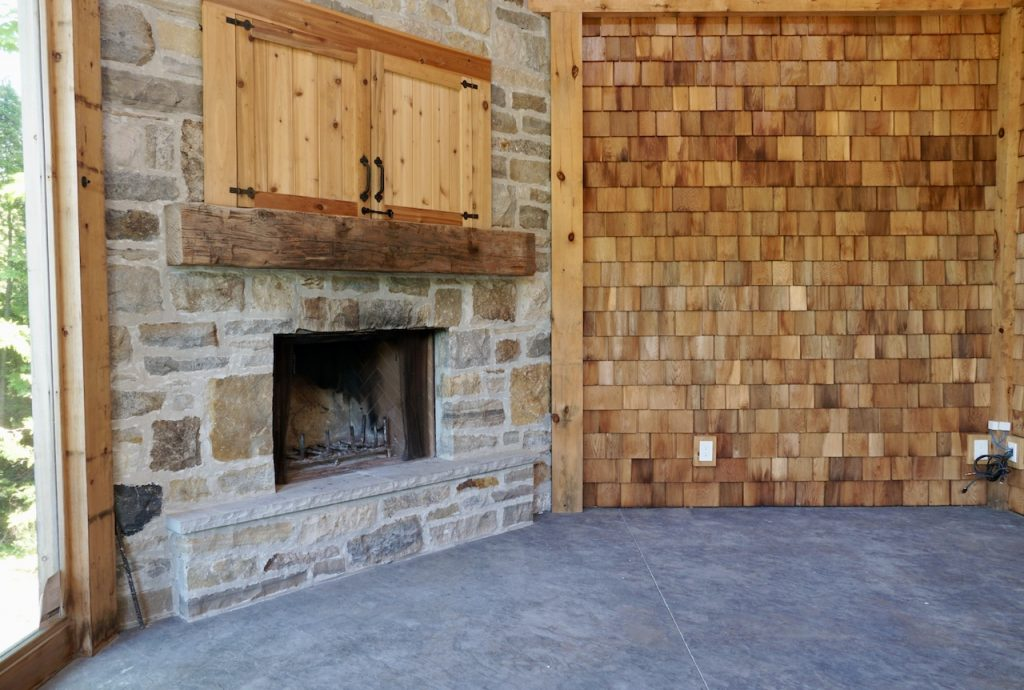Stone-fronted fireplace and cedar shingle accented walls