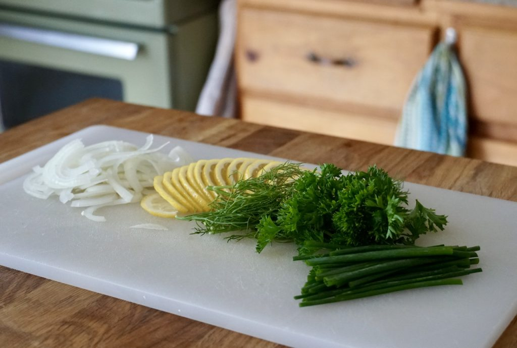Lemon, onion and fresh herbs ready to be used to stuff the fish