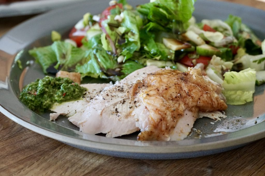 The chicken thinly sliced serted with a salad and a dollop of chimichurri