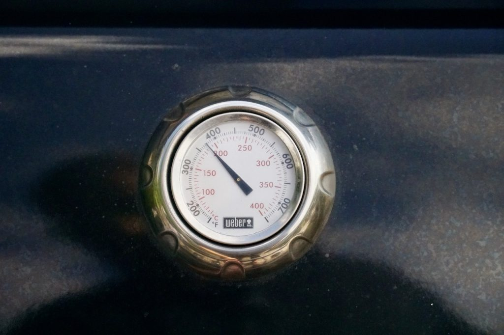 Setting the barbecue to a consistent 375°F.