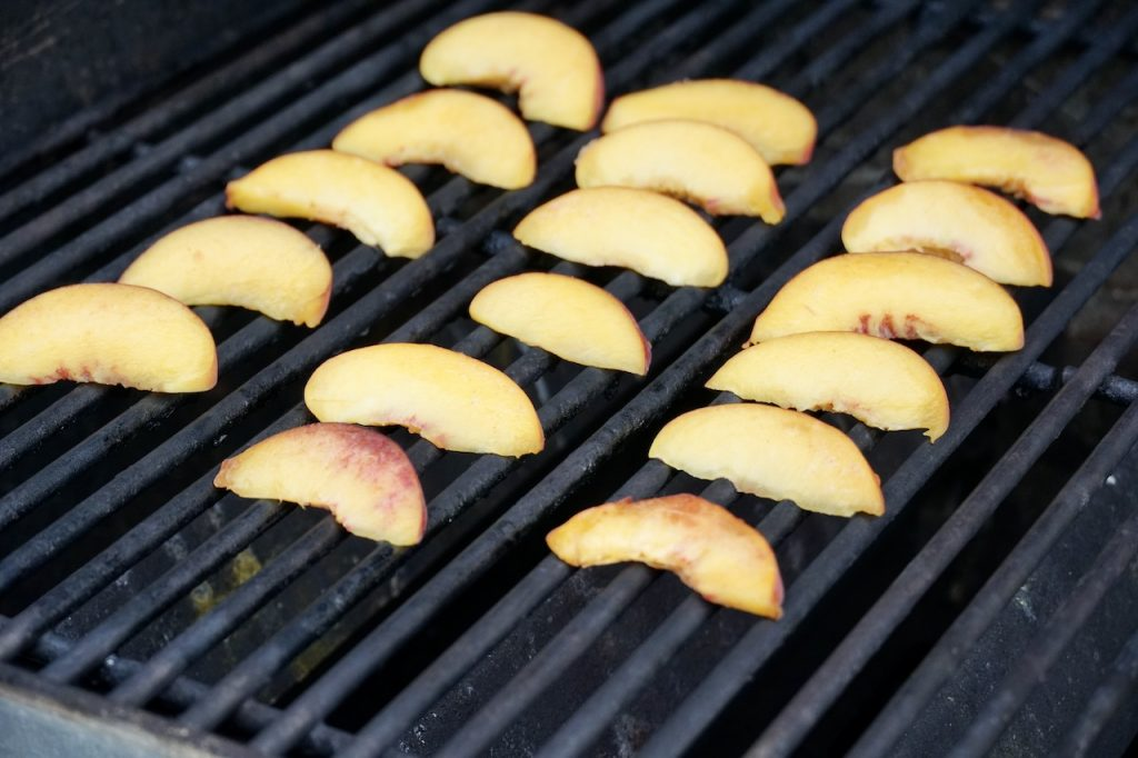 The peach slices on the grill