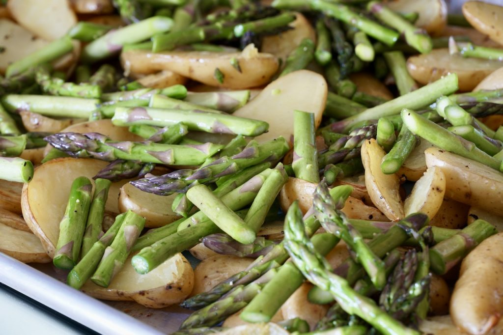 The asparagus and potatoes spread out on the sheet pan